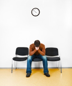 Man in waiting room with a clock on wall with head in hands