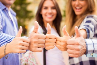 Close up photo of group of happy students showing thumbs up