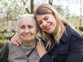 Elderly woman with cheerful caregiver outdoor, springtime