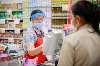 female supermarket cashier in medical protective mask working at supermarket